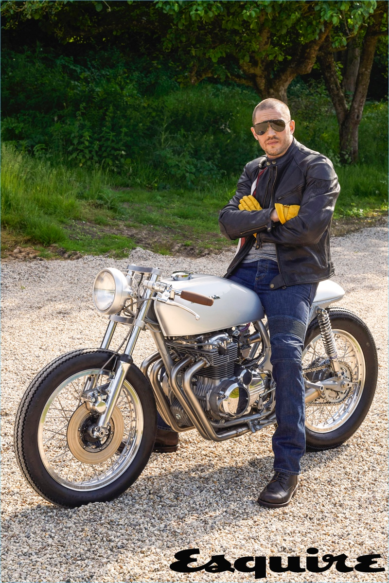Sitting on a bike, Tom Hardy wears a leather jacket and jeans by Belstaff. He also sports an Alternative Apparel t-shirt, Triumph boots, and Carrera sunglasses.