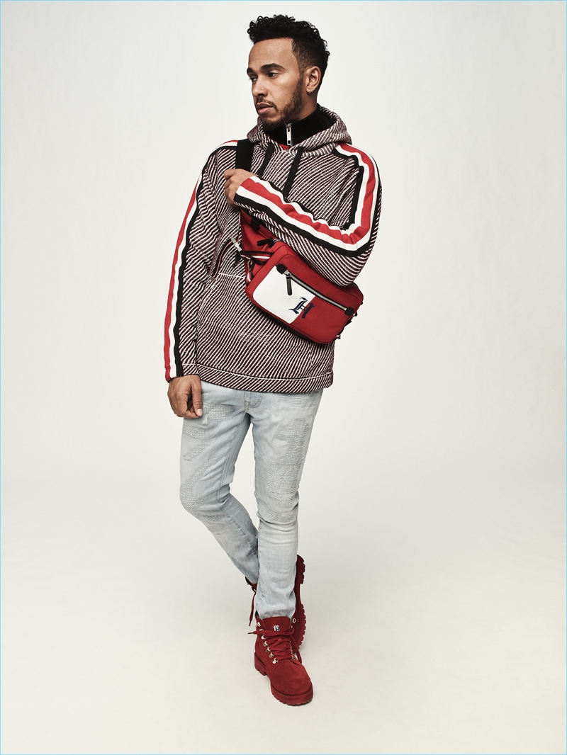 A casual vision, Lewis Hamilton rocks a belt bag, hoodie, velvet track jacket, jeans, and boots from his Tommy Hilfiger collaboration.