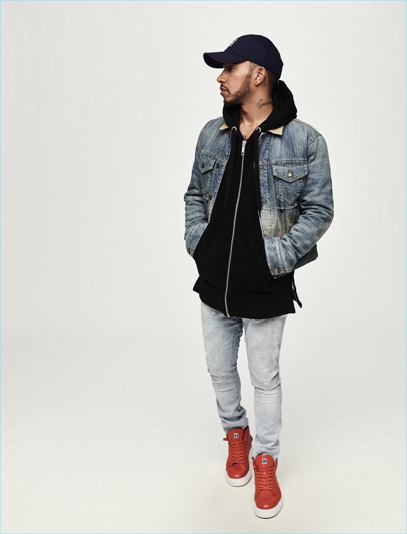 Dobrado em denim, Lewis Hamilton veste uma jaqueta jeans, moletom com capuz, jeans, boné e tênis de sua coleção Tommy Hilfiger.