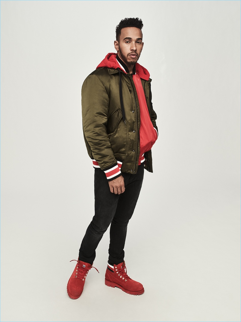 Donning a bomber jacket, Lewis Hamilton also wears a souvenir jacket, jeans, and hiking boots from his Tommy Hilfiger collection.