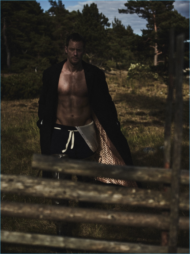 Posing for a dramatic photo, Alexander Skarsgård dons a Haider Ackermann coat, Alias Costume Rental longjohns, and Cassie Mercantile pants.