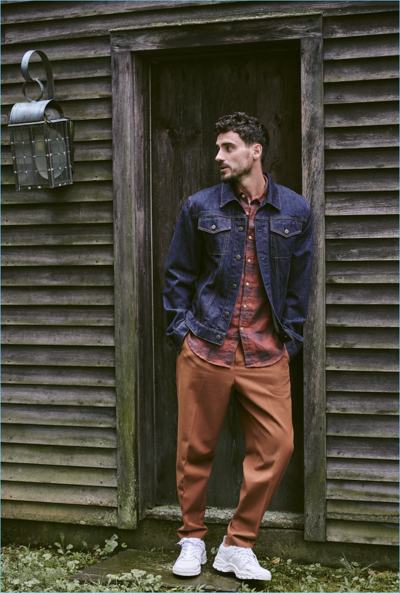 Arthur Kulkov wears a Helmut Lang denim jacket, Portuguese flannel shirt, Tomorrowland pants, and AMI sneakers.