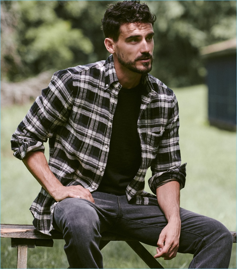 Connecting with East Dane, Arthur Kulkov wears a Vince tee and sneakers with a Gitman Vintage flannel shirt and Frame denim jeans.