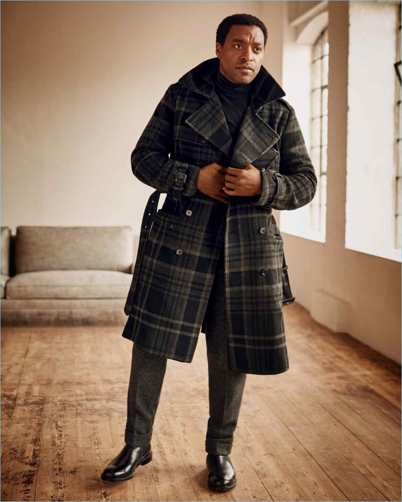 Actor Chiwetel Ejiofor sports a Ralph Lauren Purple Label trench coat, turtleneck, and trousers with Church's boots.