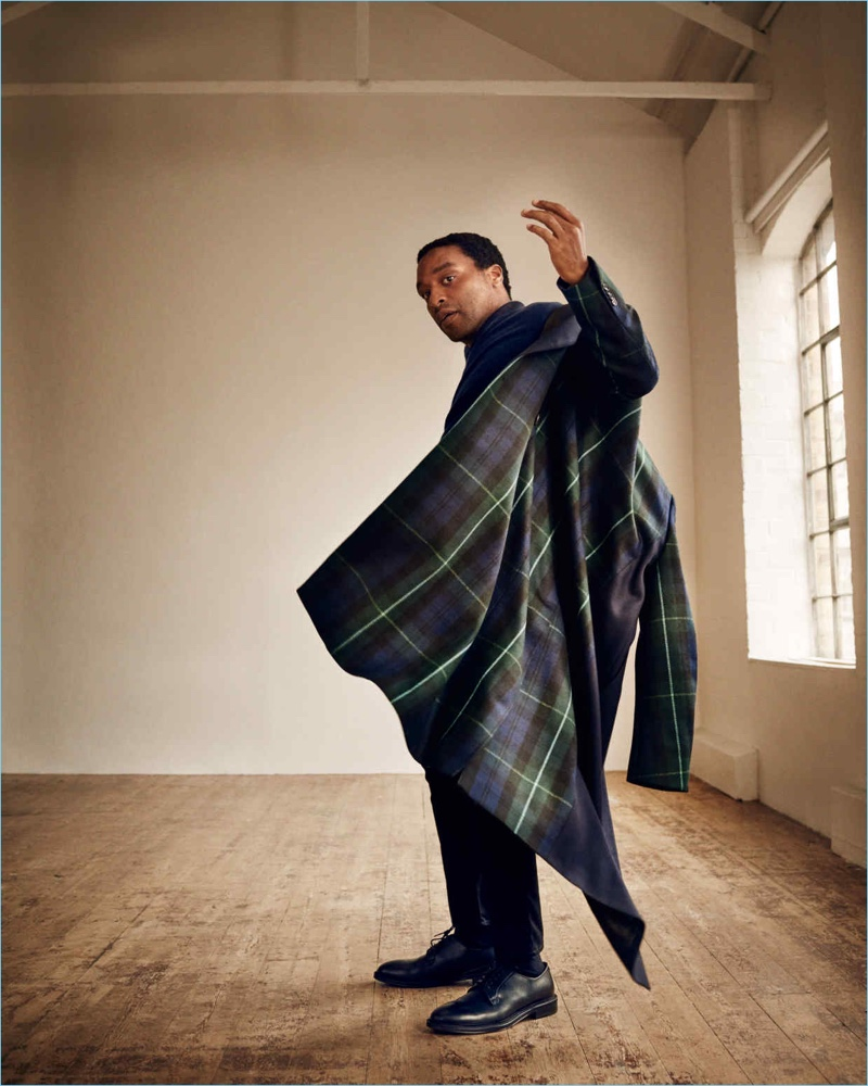 Embracing plaid, Chiwetel Ejiofor sports a Paul Smith coat and sweater with Acne Studios jeans and Mr P. derby shoes.