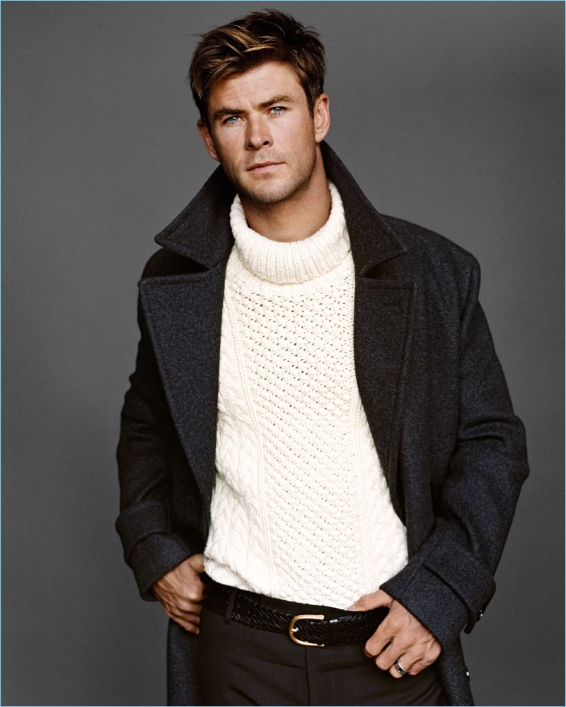 Appearing in a new photo shoot, Chris Hemsworth wears a BOSS coat, and Michael Kors sweater. He also dons a Tom Ford leather belt and pants.