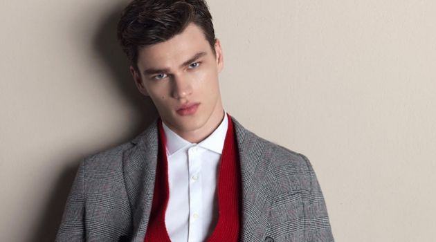 Model Filip Hrivnak wears a red cardigan with a grey suit for Gazzarrini's fall-winter 2018 campaign.