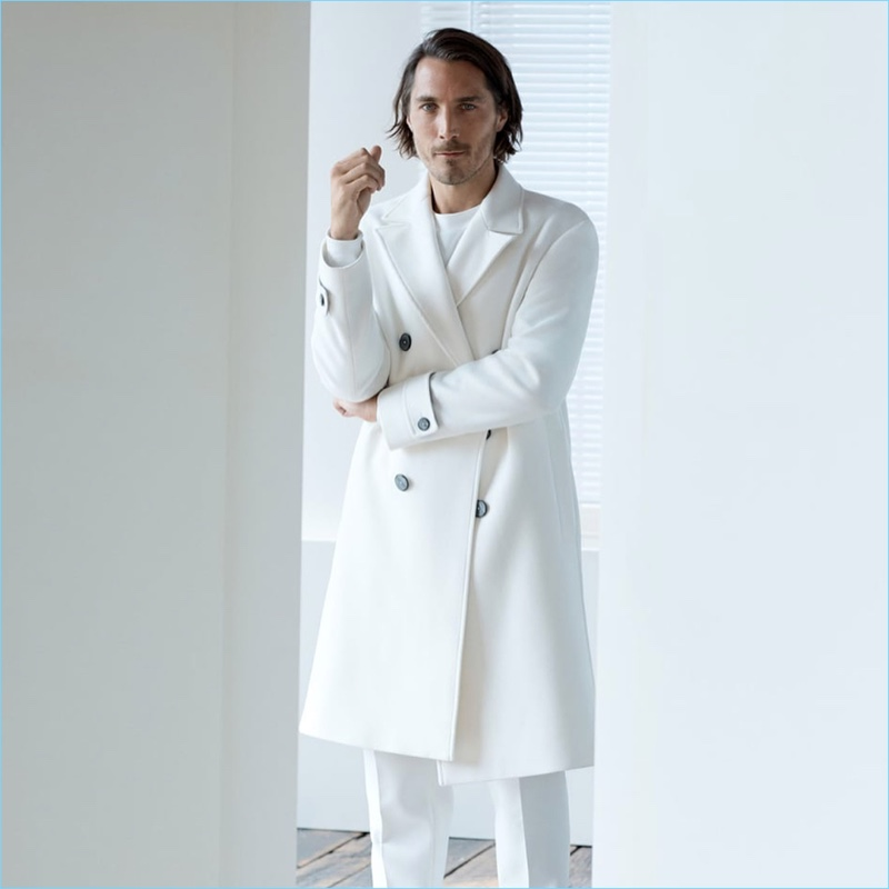 Sporting winter white, Guillaume Macé appears in an editorial for Zara.