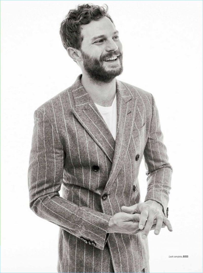 All smiles, Jamie Dornan wears a double-breasted pinstripe suit by BOSS.