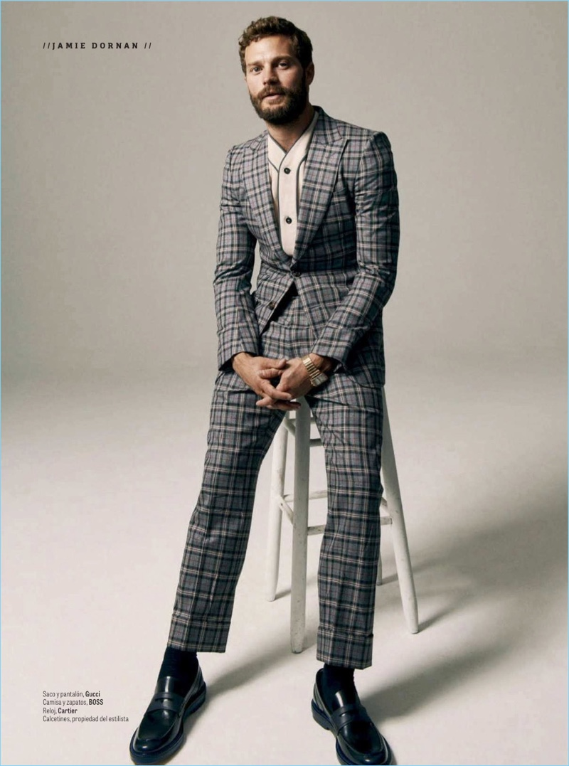 A dapper vision, Jamie Dornan dons a check Gucci suit with a shirt and shoes by BOSS. He also sports a Cartier watch.