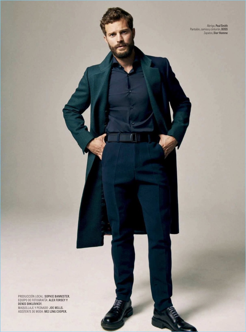 Embracing fall style, Jamie Dornan wears a Paul Smith coat with a shirt, belt, and pants by BOSS. Dior Men shoes complete his look.