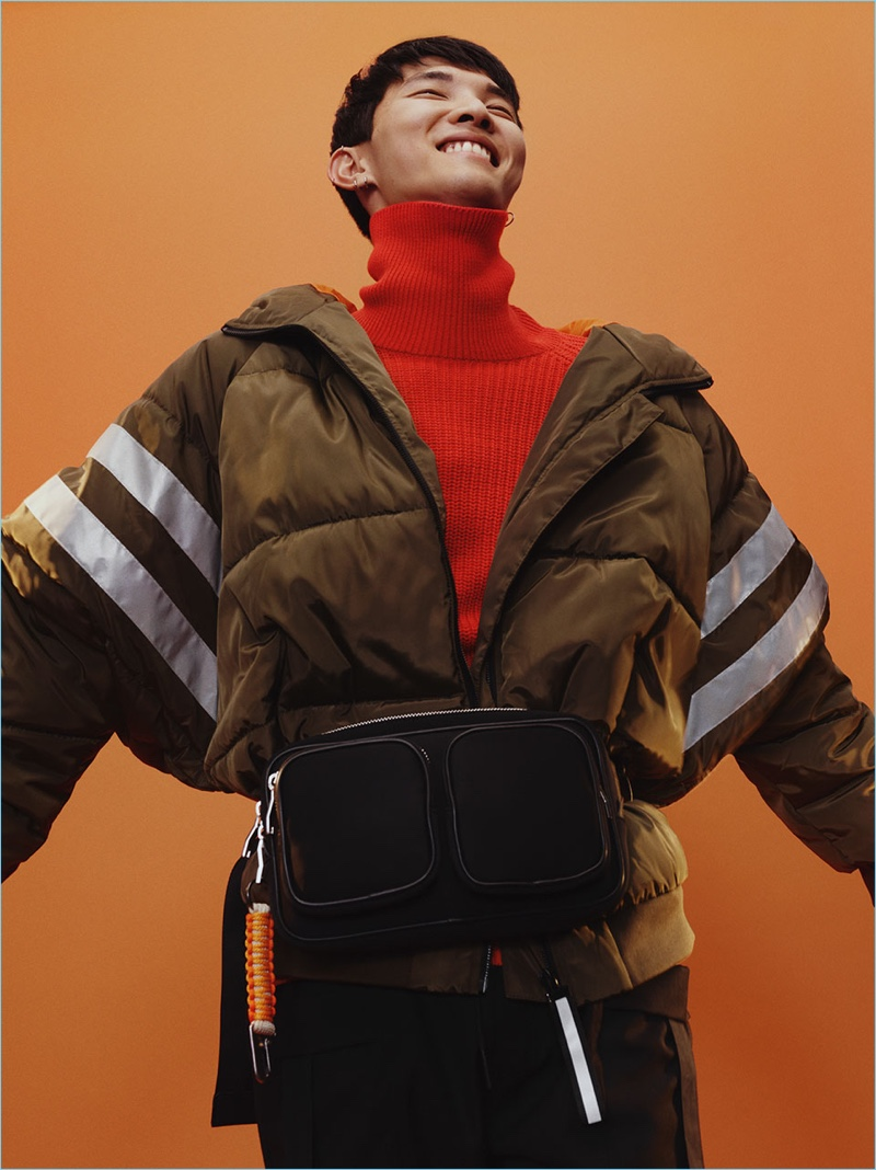 All smiles, Jeon June wears an oversized puffer jacket with a red turtleneck sweater and belt bag from Zara Man.