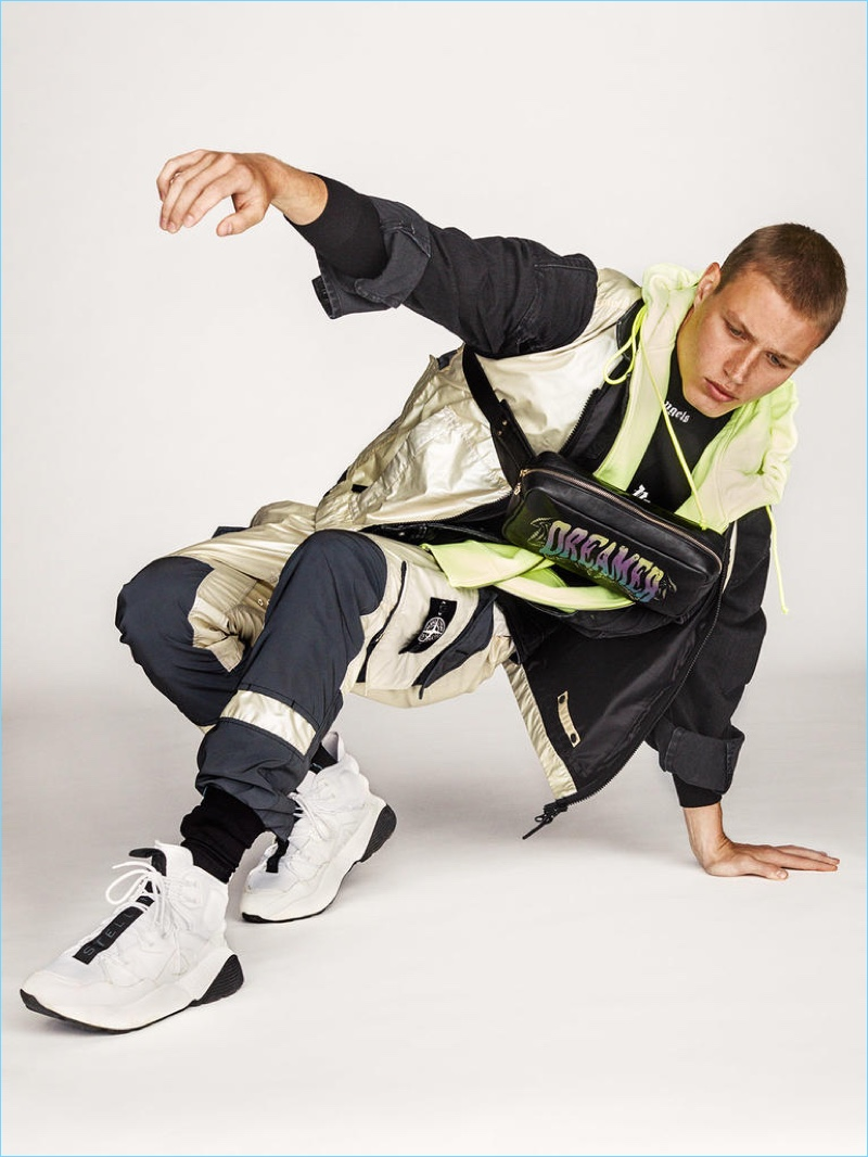 STONE ISLAND sleeveless jacket £525 and trousers £575; JUUN.J double-layer hooded jacket £875; PALM ANGELS T-shirt £210; RAF SIMONS polo neck (worn underneath T-shirt) £365; PAUL SMITH bag £495; PRADA socks £110; STELLA McCARTNEY sneakers £525