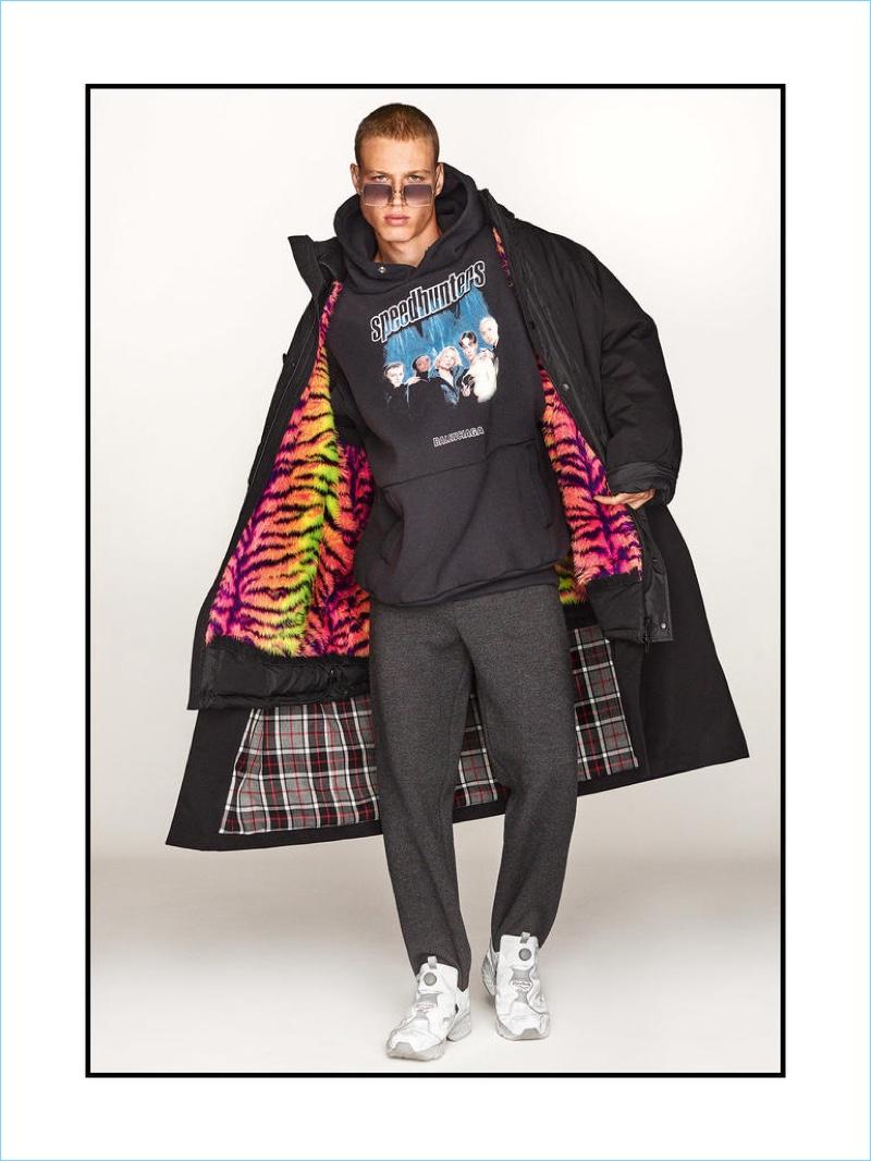 BALENCIAGA coat £3,785, hooded sweatshirt £395 and trousers £1,085; OLIVER PEOPLES sunglasses £255; VETEMENTS x REEBOK sneakers £845