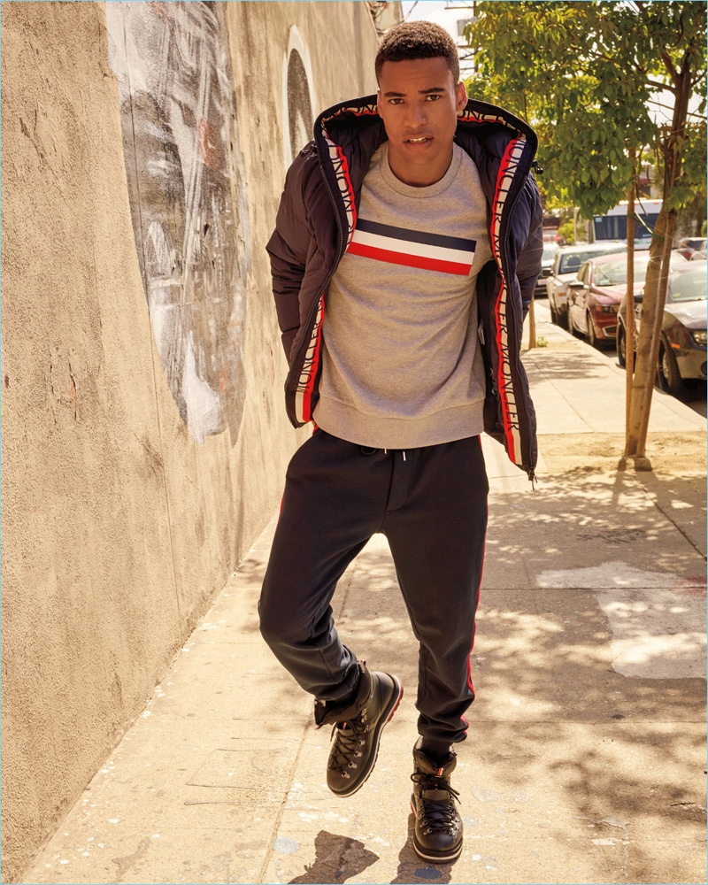Malik Lindo sports a Moncler graphic sweatshirt, puffer jacket, side-stripe pants, and hiking boots.