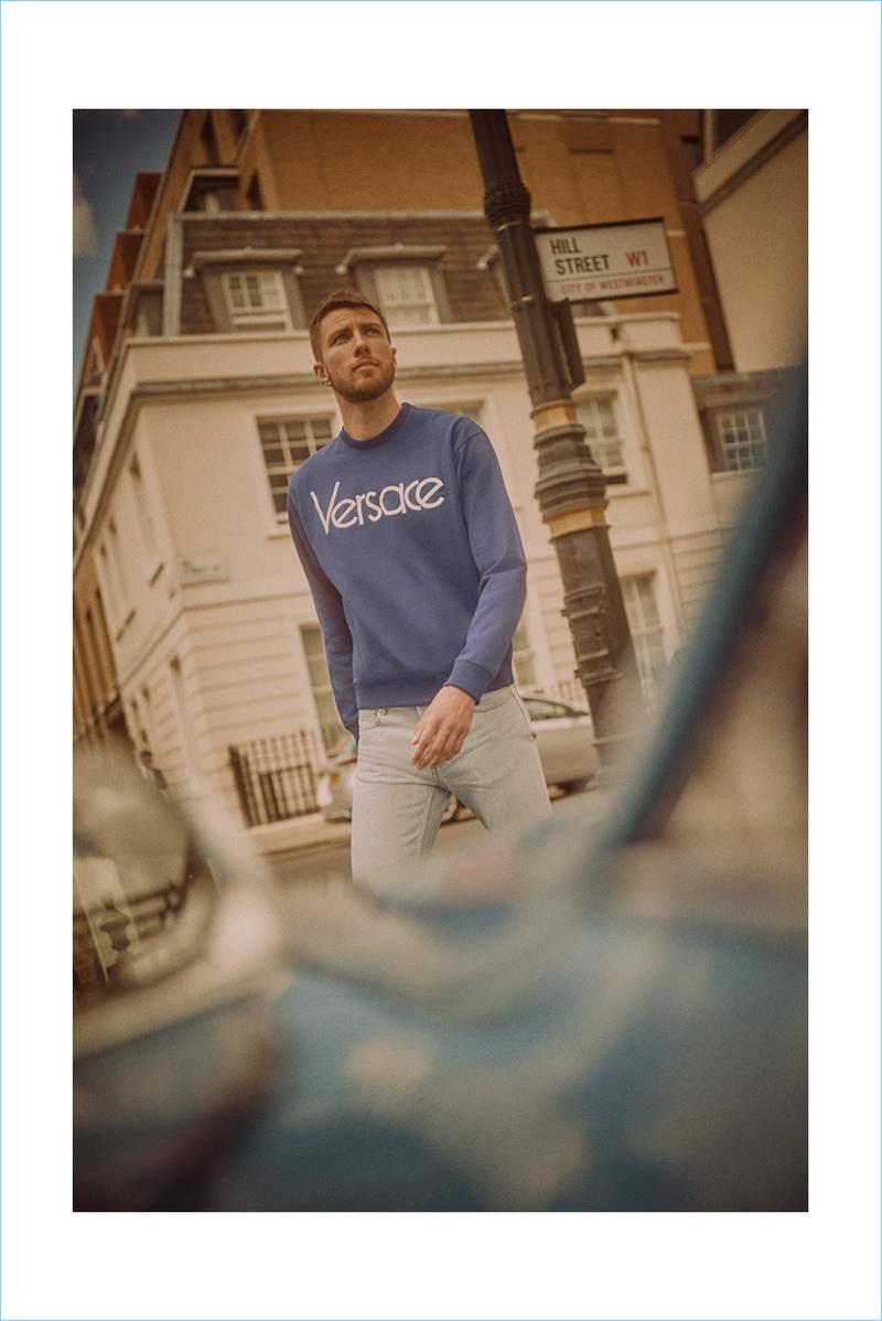 Andrew Pozzi sports a Versace logo sweatshirt, Loro Piana t-shirt, and A.P.C. jeans.
