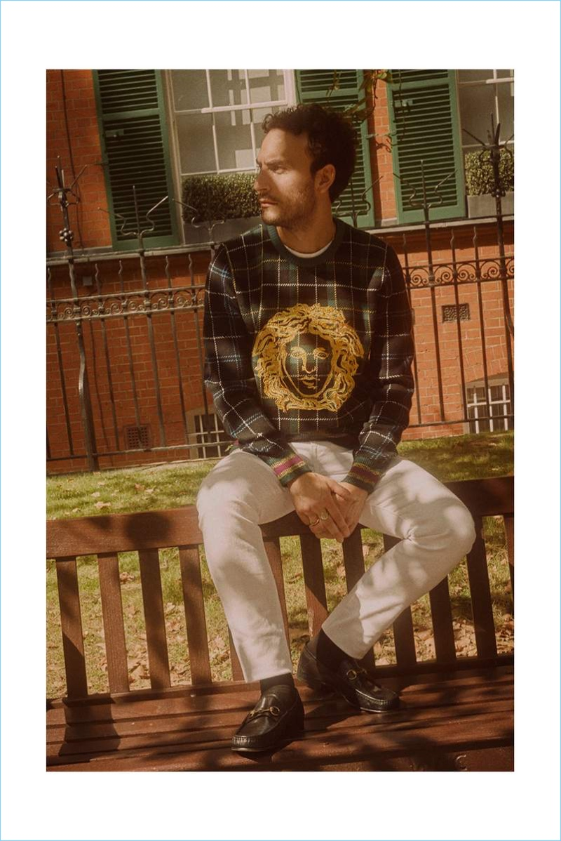Actor Cesare Taurasi rocks a Versace sweater, white Burberry jeans, and Gucci loafers.