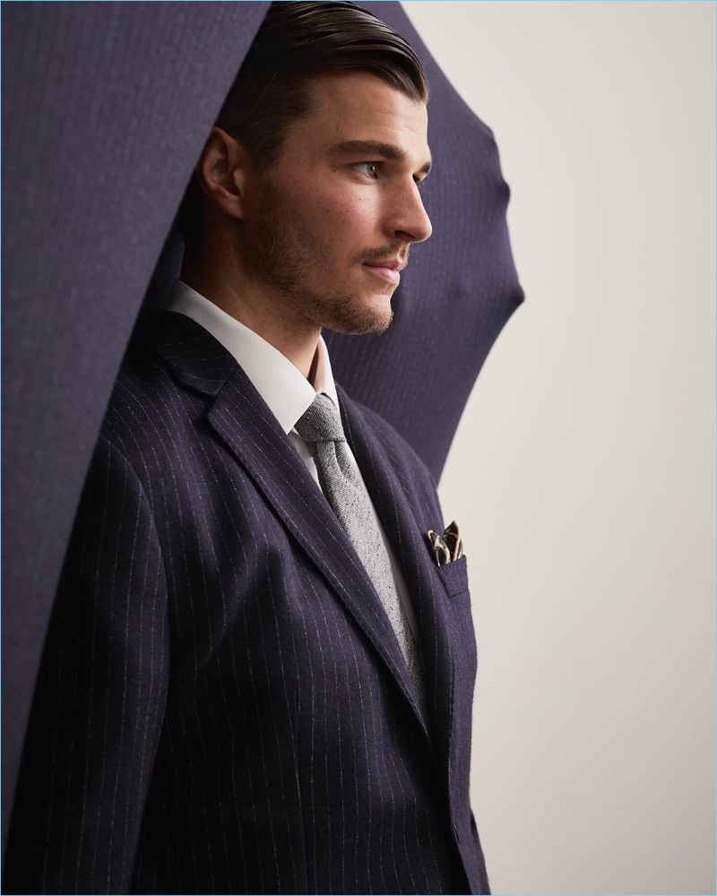 Arran Sly sports a Banana Republic x Kevin Love pinstripe suit jacket with a grey tie.