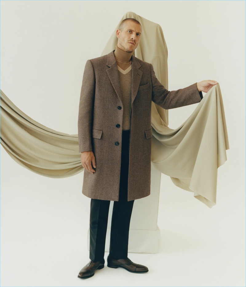 Embracing fall neutrals, Mike Guenther wears a Brioni herringbone overcoat, v-neck sweater, wool turtleneck sweater, and flat-front trousers. He also sports Crockett & Jones leather shoes.