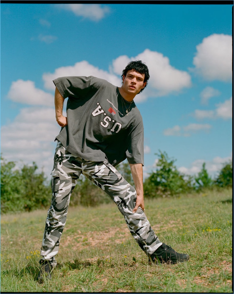 Going casual, Luka Isaac models a Willy Chavarria t-shirt, Balenciaga camouflage cargo pants and ROA sneakers.