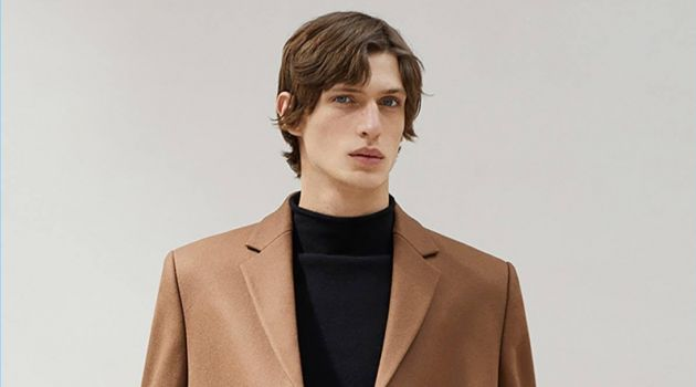 Edoardo Sebastianelli dons a brown coat and mock turtleneck sweater from COS.
