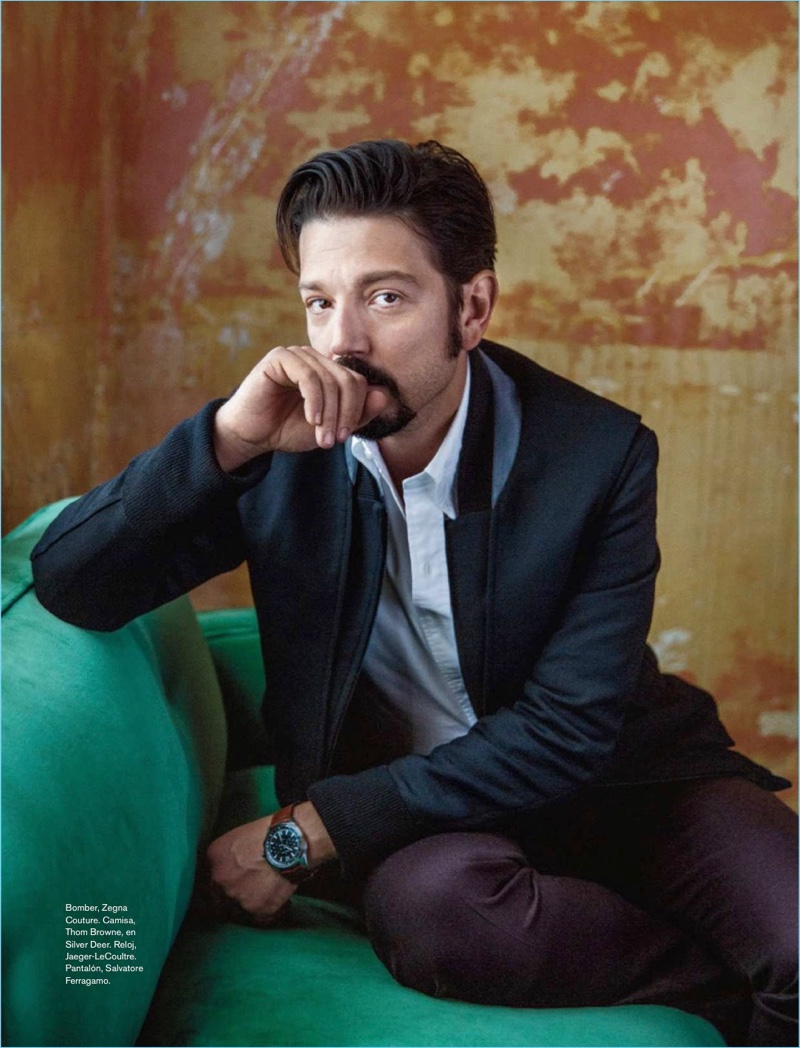 Sitting  for a photo, Diego Luna wears an Ermenegildo Zegna Couture jacket, Thom Browne shirt, Jaeger-LeCoultre watch, and Salvatore Ferragamo trousers.