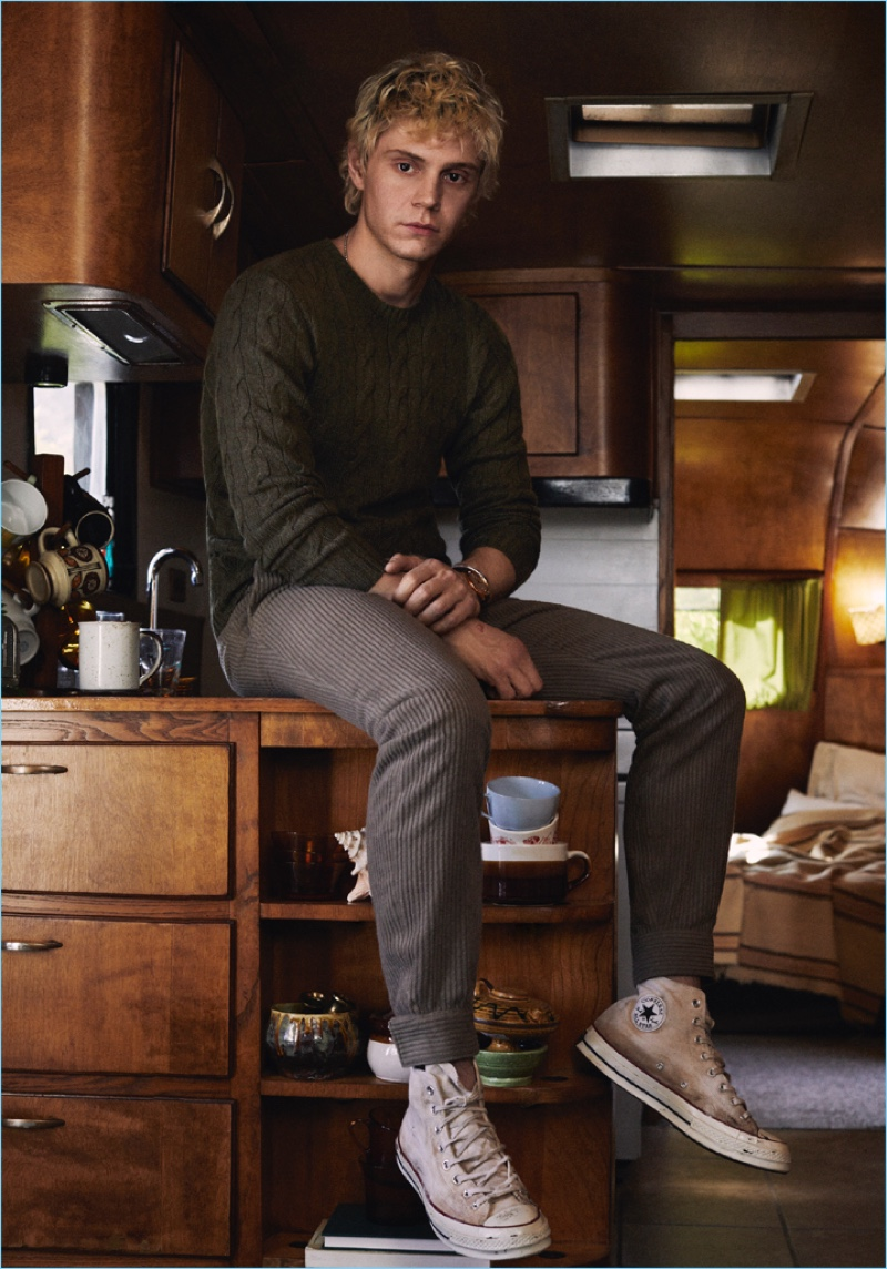 Appearing in a new photo shoot, Evan Peters dons a Ralph Lauren sweater with Ermenegildo Zegna trousers and Converse sneakers.