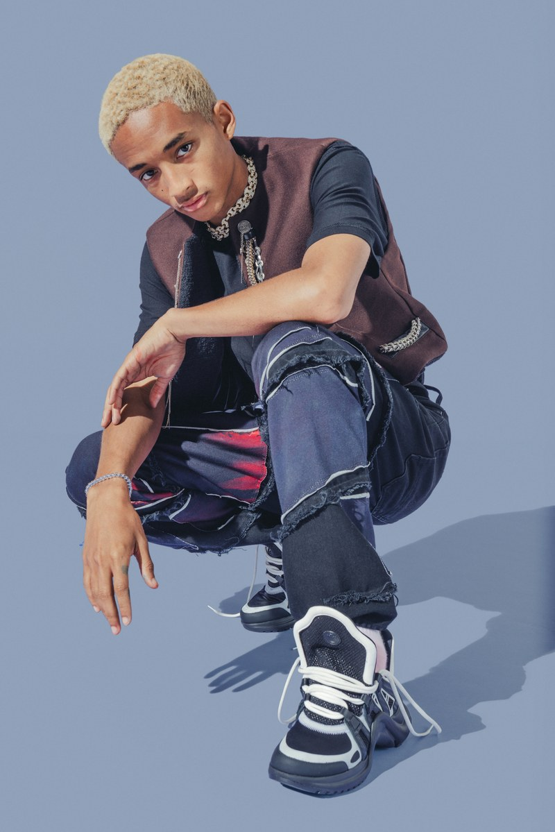 Rocking a skate-inspired look, Jaden Smith wears a Louis Vuitton vest. He also sports an MSFTS t-shirt and Louis Vuitton sneakers. Accessorized with his own jewelry, jeans from his G-Star Raw Forces of Nature collaboration complete his look.