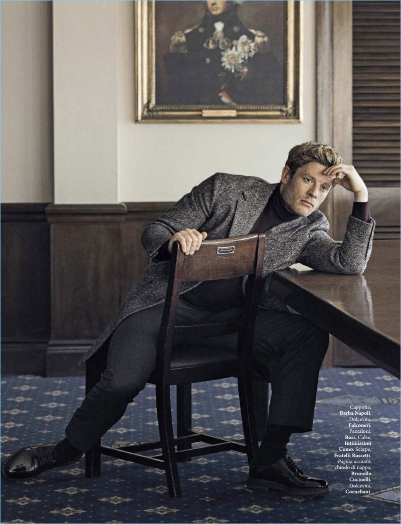 Sitting for a photo, James Norton sports a Barba Napoli coat, Falconeri turtleneck, BOSS trousers, and Fratelli Rossetti shoes.