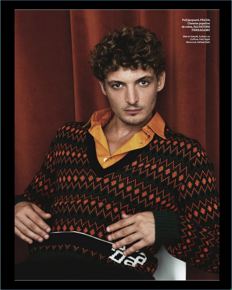 Starring in a photo shoot, Niels Schneider wears a Prada sweater with a shirt and pants from Salvatore Ferragamo.