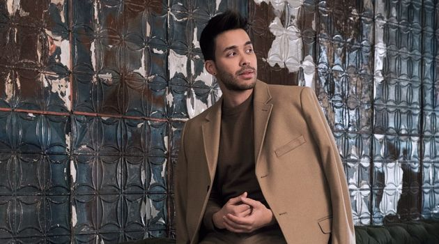 Singer Prince Royce dons a wool-blend camel coat with a fine-knit sweater, and suit pants by H&M.