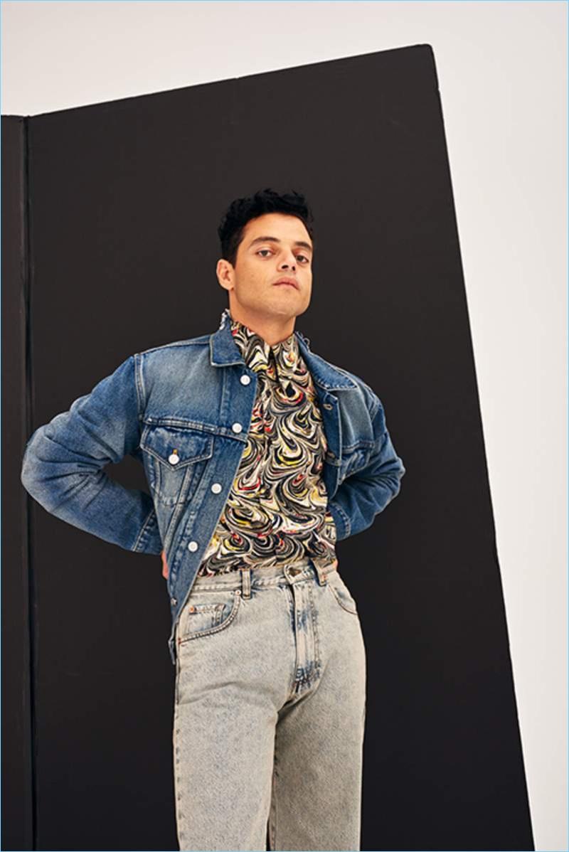 Going casual, Rami Malek wears a Balenciaga denim jacket, Dries Van Noten shirt, and Gucci jeans.