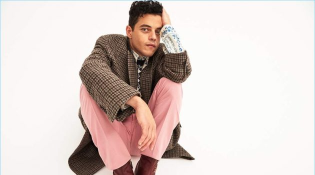 Rami Malek wears a Balenciaga checked coat with a shirt, boots, and sweater vest by Gucci. He also dons pink Alexander McQueen trousers.