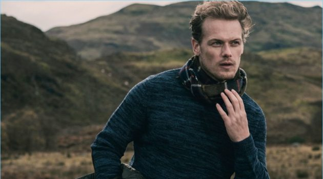 Appearing in a new photo, Sam Heughan dons a lambswool sweater from his Barbour collaboration.