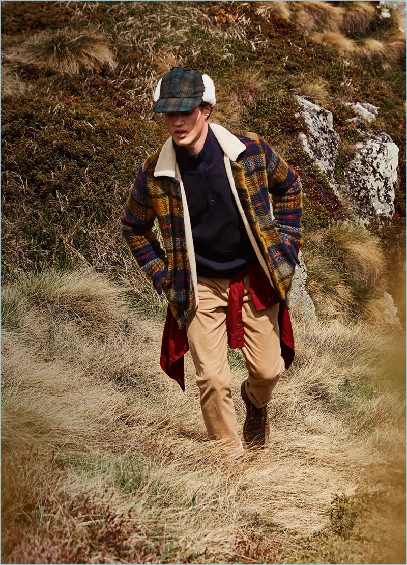 Starring in Scotch & Soda's fall-winter 2018 campaign, Benjamin Reynier wears a checked wool jacket. Venturing outdoors, he also sports a half-zip pullover, garment-dyed shirt, corduroy trousers, and a checked trapper hat.