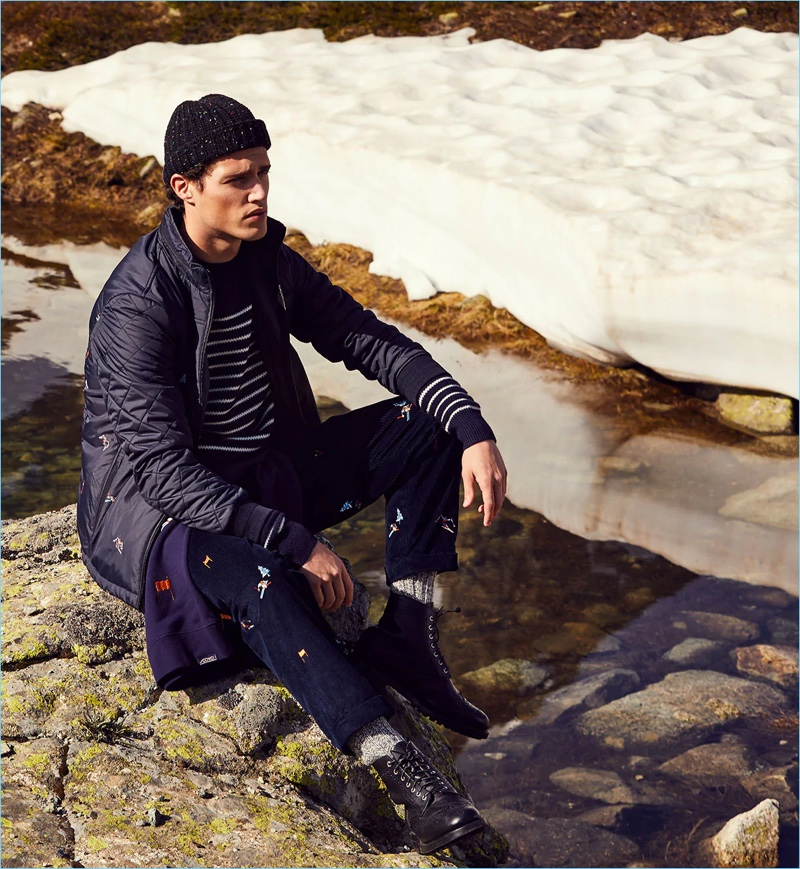 Connecting with Scotch & Soda for fall-winter 2018, Benjamin Reynier wears an embroidered jacket, striped sweater, ski artwork corduroy pants, and a chunky beanie.