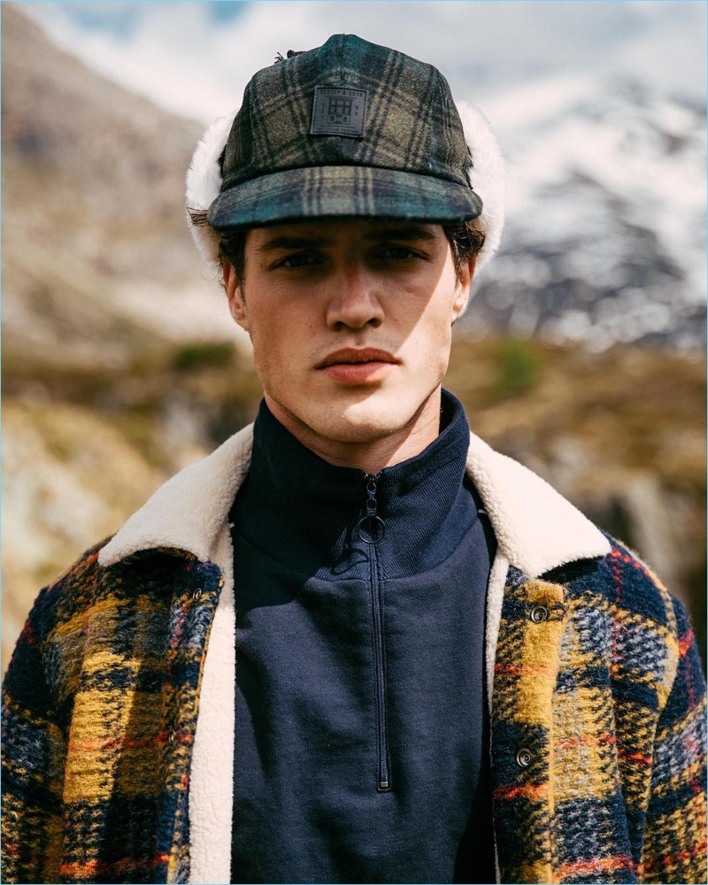 Front and center, Benjamin Reynier models a Scotch & Soda checked wool jacket and trapper hat with a half-zip pullover.