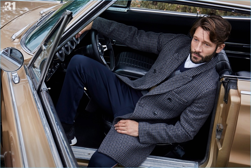 Relaxing in a vintage car, John Halls dons a LE 31 check overcoat, argyle sweater, officer collar shirt, , and piqué-stripe athletic pants.