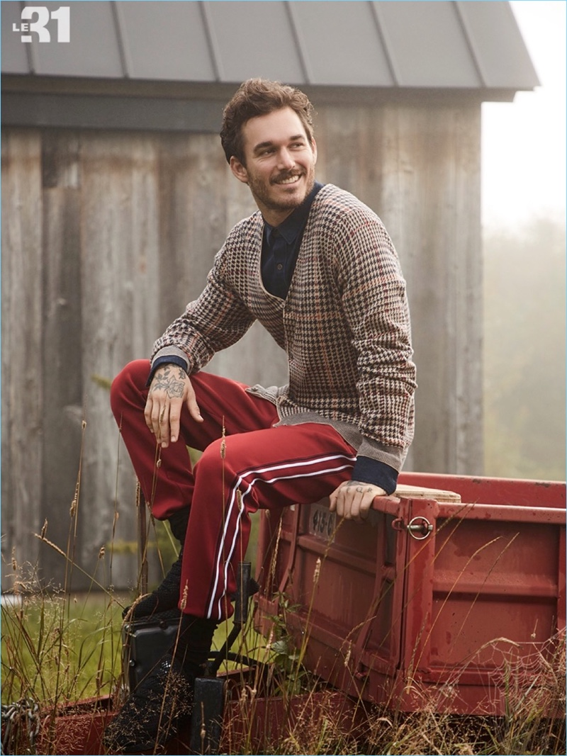 All smiles, David Alexander Flinn wears a LE 31 houndstooth cardigan, chambray jean shirt, and striped athletic pants.