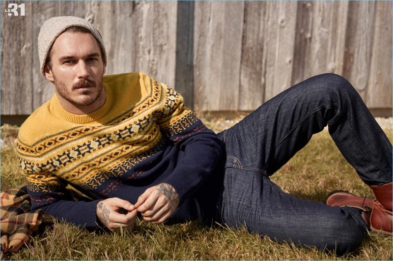 Relaxing, David Alexander Flinn wears a LE 31 Scandinavian jacquard sweater and knit beanie with Levi's deep indigo 511 jeans.