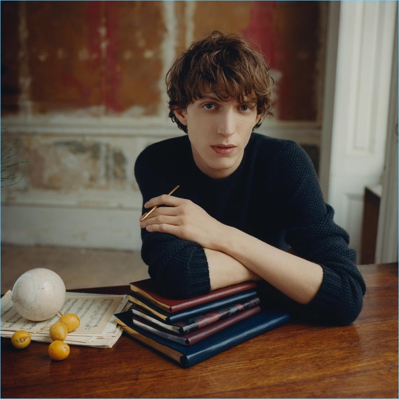 Sitting for a photo, Xavier Buestel poses with Smythson's leather-bound notebooks.