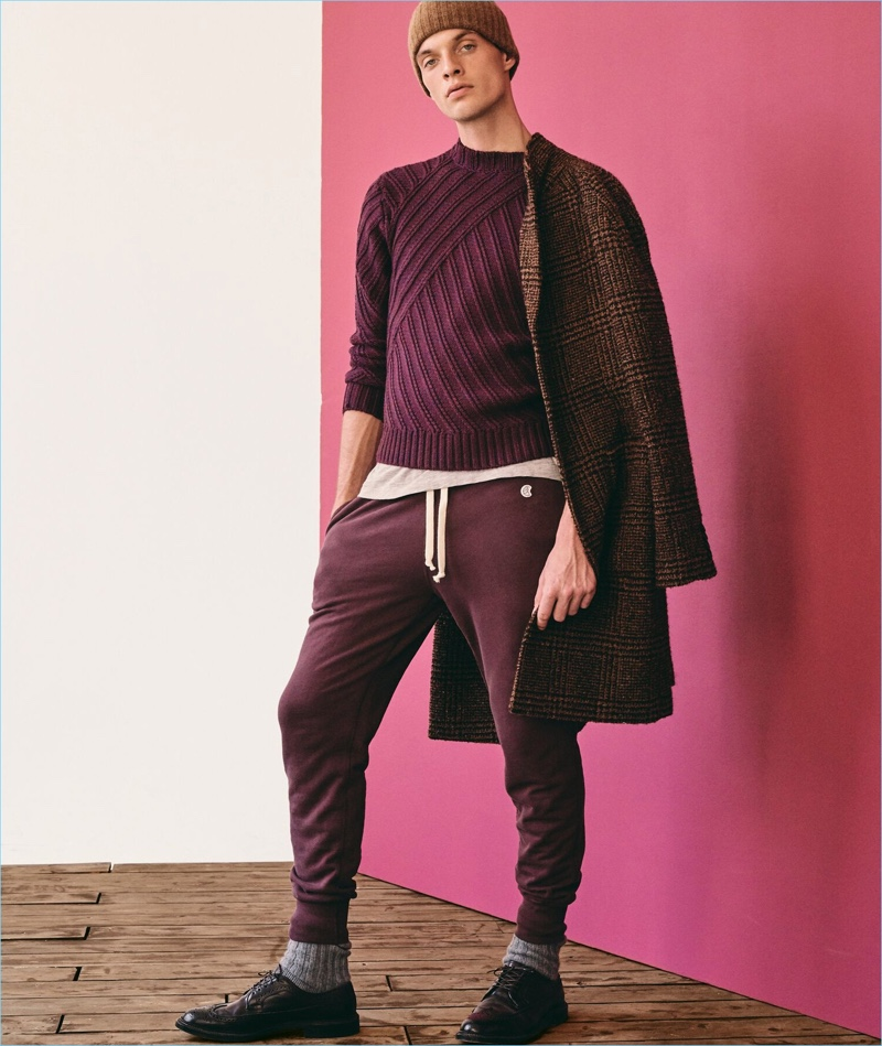Warming up to autumnal hues, Rocky Harwood wears a hand-knit maroon cable crewneck sweater by Todd Snyder.