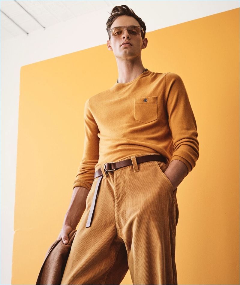 Making a colorful statement, Rocky Harwood wears a gold yellow cashmere t-shirt sweater from Todd Snyder.