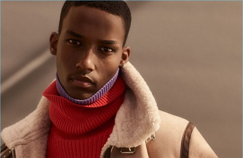 Mahad Musse dons a shearling aviator jacket and knit turtleneck sweaters from Zara Man.