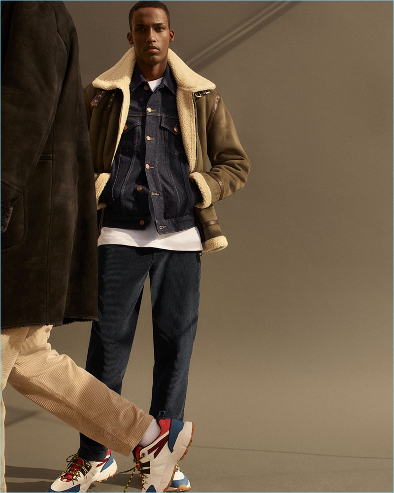 Connecting with Zara, Mahad Musse sports a khaki aviator jacket, raw denim jacket, corduroy trousers, and sneakers.
