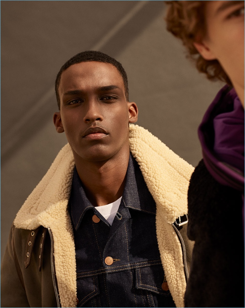 Model Mahad Musse wears khaki aviator jacket and raw denim jacket from Zara Man.