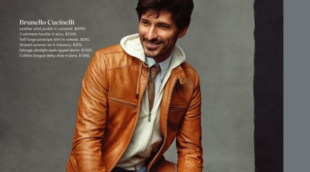 All smiles, Andres Velencoso dons a Brunello Cucinelli caramel leather jacket, cashmere hoodie, pinstripe shirt, striped tie, ripped jeans, and brogue derby shoes.