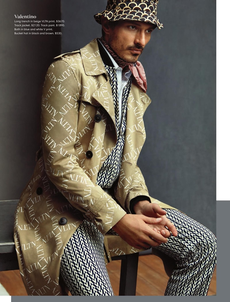 Making a printed statement, Andres Velencoso wears a Valentino logo print trench coat, track suit, and bucket hat.