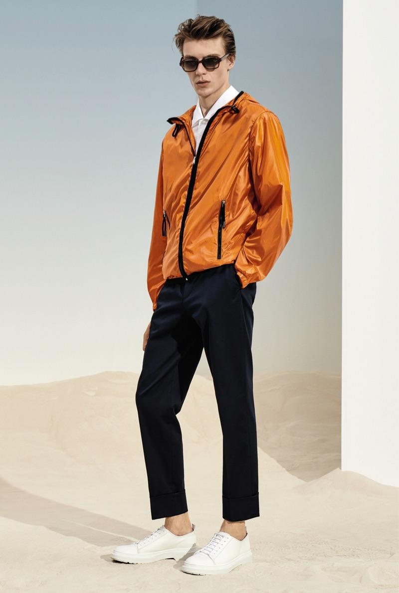 Embracing a pop of color in an orange jacket, Finnlay Davis wears BOSS.