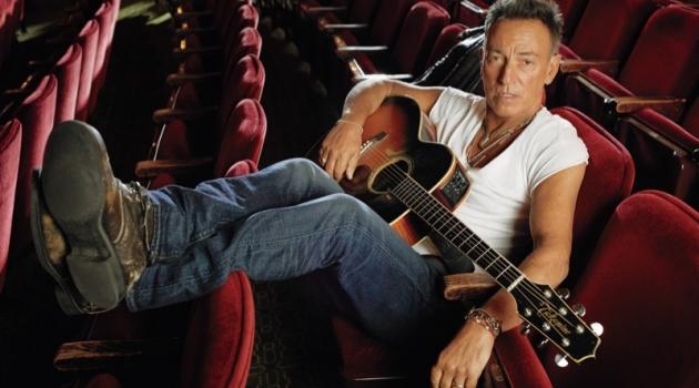 Kicking his feet back, Bruce Springsteen sports an AllSaints t-shirt.
